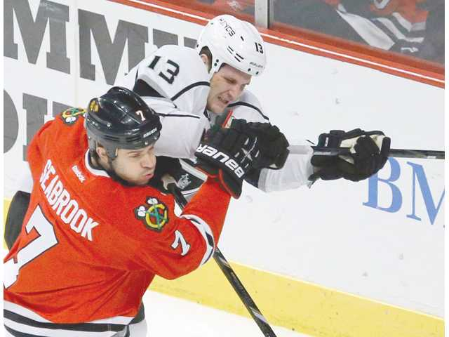 Chicago Blackhawks defenseman Brent Seabrook (7) and Los Angeles Kings left wing Kyle Clifford battle for a loose puck on Monday in Chicago.