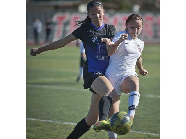 Valencia's Bailey Reid fights for possession of the ball against Hart midfielder Sophia Cortes at Hart High School on Monday.
