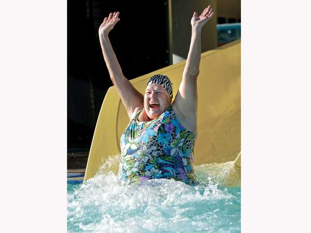 Irvitte Smith from Sylmar raises her arms as she enters the chilly waters at the aquatics center to start out the new year. Photo by Jayne Kamin-Oncea for The Signal.