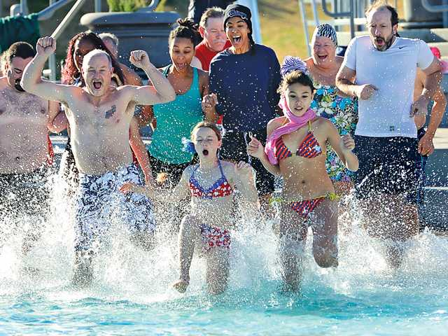 Some of the more than 100 polar plungers race into the chilly waters at the Santa Clarita Aquatic Center on Wendesday.Photo byJayne Kamin-Onceafor The Signal.