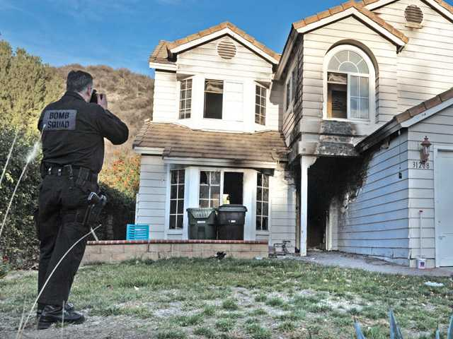 Sheriff's arson unit Detective Edward Nordskog photographs the house in the 31200 block of Quail Valley Road in Castaic during his investigation on Thursday. Signal photo by Dan Watson