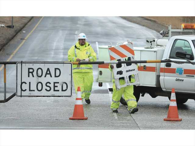 In the Signal file photo, Caltrans workers wearing rain gear carry barriers to the closed gate at the entrance of the on-ramp to the north-bound Interstate 5 freeway on Lake Hughes Road in Castaic.