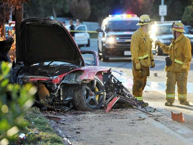 Firefighters stand near the wreckage of a Porsche that hit a light pole and burned in Valencia Nov. 30, killing Paul Walker and Roger Rodas. Signal photo by Dan Watson