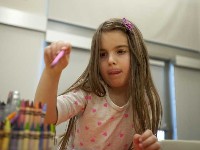 Chloe Thoman picks out crayons for an art project on Friday during an ARTree event at Newhall Library. Signal photo by Charlie Kaijo