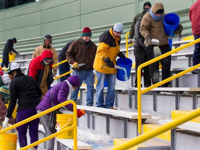 Workers clear ice and snow from the seats at Lambeau Field on Friday to preapre for Sunday's NFL football wild-card playoff game between the Packers and 49ers.