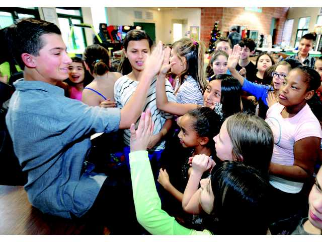 Griffin Peters, 16, left, high-fives kids at the Boys & Girls Club in Newhall after he presented a check for $10,850.00 to the organization on Friday.