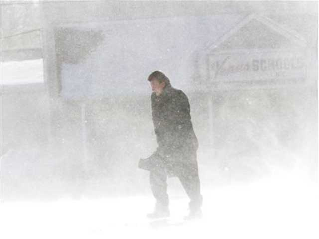 A pedestrian walks through drifting snow along Chester Pike in Sharon Hill on Friday, Jan. 3, 2014.