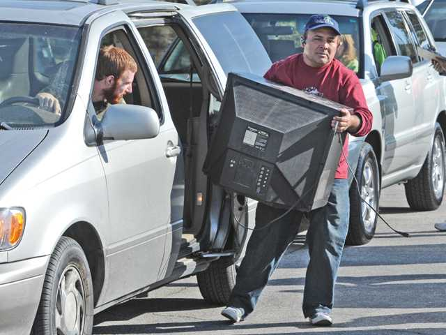 Greenview Recourse Management worker Armando Orantes removes a TV from a minivan that has lined up at the e-waste recycling benefit for Hart High School in the College of the Canyons parking lot.
