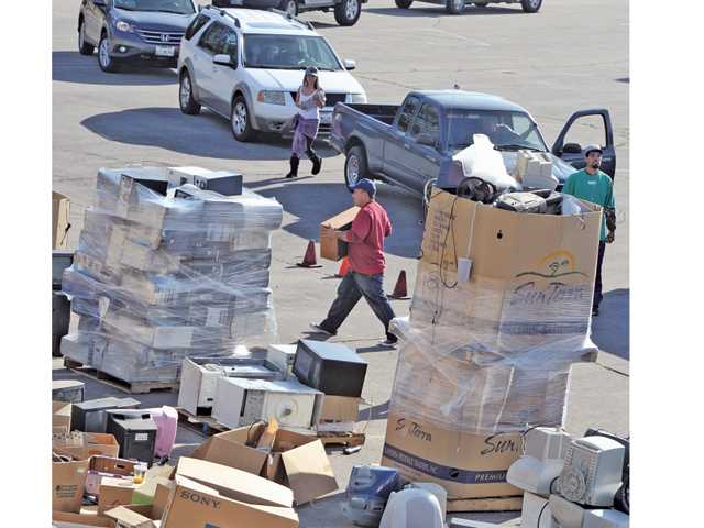 Cars line up to drop off unwanted electric items amid hundreds of pounds of old electronics piled on pallets for recycling at the event.