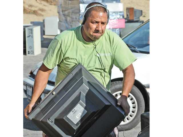 Greenview Recourse Management worker Jimmy Ortiz stacks a television on a pile of unwanted electronic items on a pallet for removal at the event.