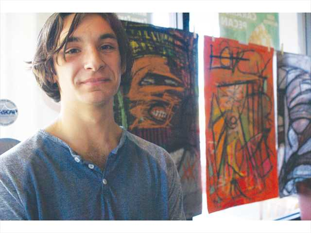 "West Ranch High School senior and artist Maxwell Schwarz stands next to his work titled, ""Terrorist #1,"" at Sunday's 2014 Art Exhibition at the It's A Grind coffee shop in Castaic. The exhibition featured the work of several West Ranch High School art program students. Signal photo by Jim Holt."