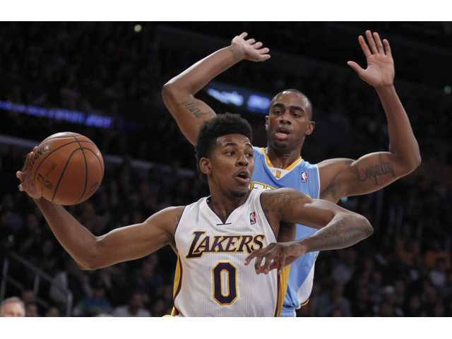 Los Angeles Lakers forward Nick Young (0) drives inside of Denver Nuggets forward Darrell Arthur on Sunday in Los Angeles.