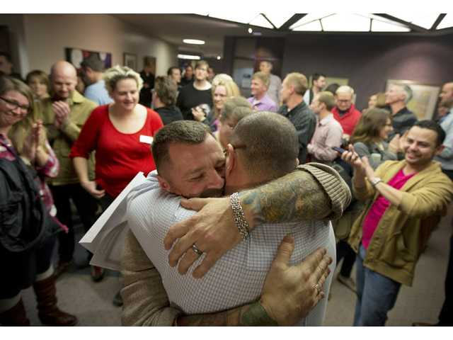 In this Dec. 20, 2013 file photo, Chris Serrano, left, and Clifton Webb embrace after being married, as people wait in line to get licenses outside of the marriage division of the Salt Lake County Clerk's Office in Salt Lake City.
