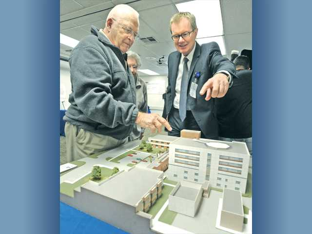Valencia resident Roger Hitzeman, left, and Henry Mayo Newhall Memorial Hospital Chief Operating Officer John Schleif discuss the model of the new patient tower at the Henry Mayo Newhall Memorial Hospital master plan open house to exhibit upcoming improvements to the hospital. Signal photo by Dan Watson.