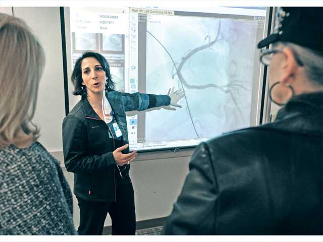 Cardiovascular Services Program Coordinator Tamar Avakian shows an X-ray video of a coronary artery for the attendees at Henry Mayo Newhall Memorial Hospital master plan open house to exhibit upcoming improvements to the hospital. Signal photo by Dan Watson.