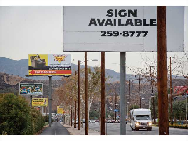 Billboards line the sidewalk along Soledad Canyon Road and Golden Valley Road. A new proposal calls for the removal of 118 signs throughout the city in exchange for the right to build three electronic billboards on city-owned land. Signal photo by Charlie Kaijo.