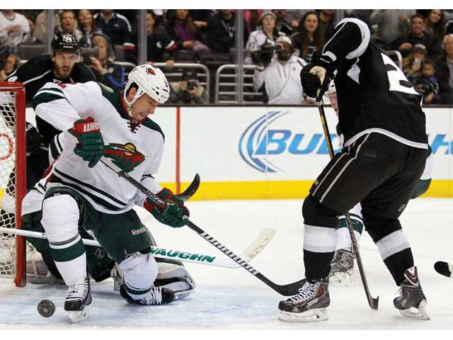 Minnesota Wild defenseman Keith Ballard, left, deflects a shot by Los Angeles Kings center Trevor Lewis on Tuesday in Los Angeles.