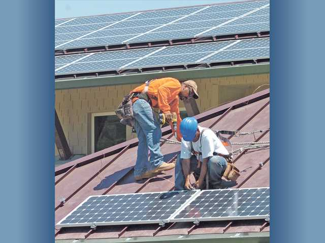 In this Signal file photo, workmen install some of 202 solar panels on the roof of the new Newhall County Water District Administration building.