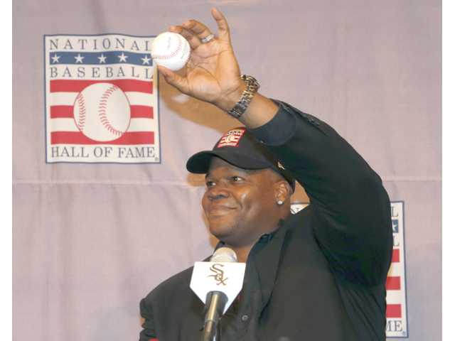 Chicago White Sox slugger Frank Thomas holds up a baseball he signed during a news conference about his selection into the MLB Hall Of Fame Wednesday.