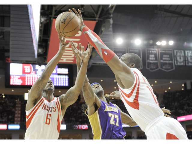 Houston Rockets Terrence Jones (6) and Dwight Howard, right, reach for a loose ball against Los Angeles Laker Jordan Hill in Wednesday's game in Houston.