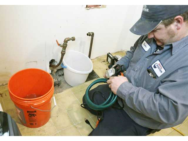 Plumber Nate Petersen prepares a pump to shoot water into the incoming city water line, left, pipe that has been frozen Thursday at a south Minneapolis home.