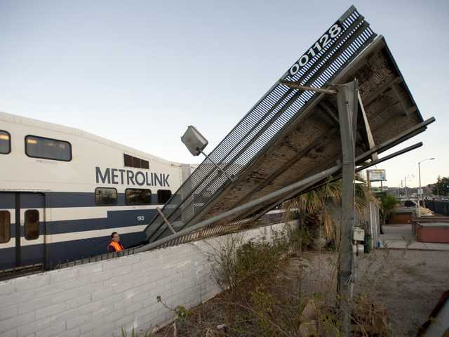 A representative from Metrolink assess the damage from a billboard that toppled over on Railroad Avenue between 15th Street and 16th Street in Newhall on Thursday. Signal photo by Charlie Kaijo.