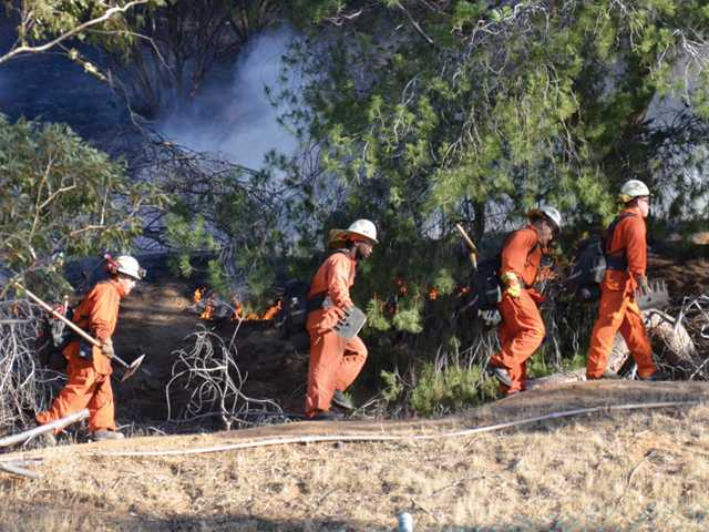 In this courtesy photo from Rick Herrmann Photography, crews carry their tools up a hill as they get a handle on the brush fire that burned about 1.5 acres in Saugus on Thursday.