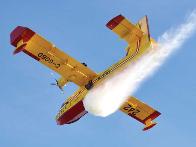 In this courtesy photo from Rick Herrmann Photography, one of the two Super Scoopers on loan from Canada makes a drop on a small brush fire in Saugus on Thursday.