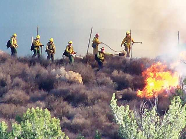 In this courtesy photo taken by Saugus resident Donna Spencer, fire crews work to douse a small brush fire in the 22400 block of Pamplico Drive in Saugus Thursday afternoon.