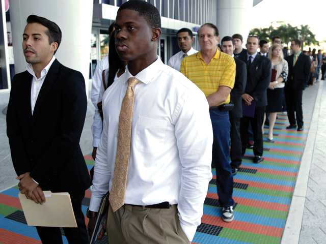 In this Wednesday, Oct. 23, 2013, file photo, Luis Mendez, 23, left, and Maurice Mike, 23, wait in line at a job fair held by the Miami Marlins, at Marlins Park in Miami. Employers added a scant 74,000 jobs in December after averaging 214,000 in the previous four months. The Labor Department said Friday, Jan. 10, 2014, that the unemployment rate fell from 7 percent in November to 6.7 percent, its lowest level since October 2008. But the drop occurred mostly because many Americans stopped looking for jobs. Once people without jobs stop looking for one, the government no longer counts them as unemployed.