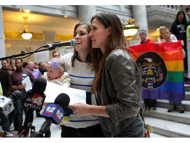Megan, left, and Candace Berrett, right, hold their daughter Quinn as they speak to supporters of gay marriage during a rally at the Utah State Capitol on Friday in Salt Lake City.