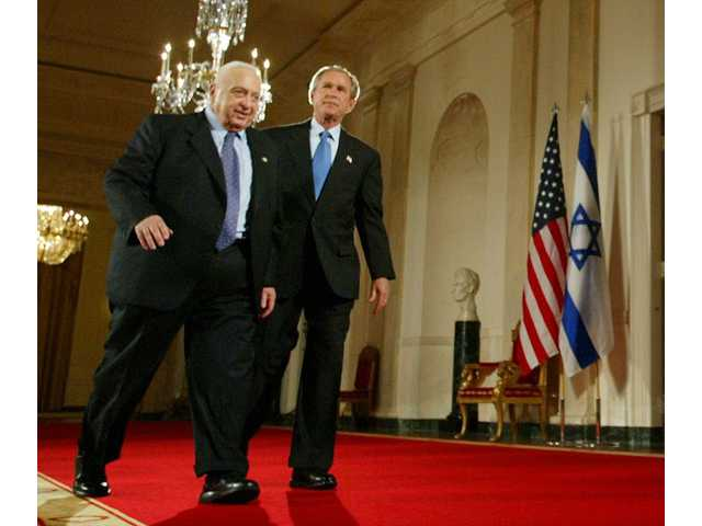 In this April 14, 2004 file photo, former President George W. Bush, right, and Israeli Prime Minister Ariel Sharon, left, walk together at the White House in Washington.