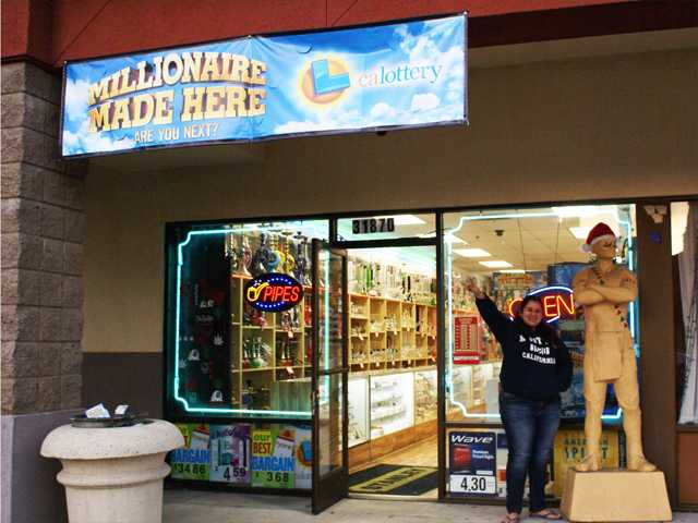 Smoke 4 Less employee Brenda Gonzalez stands outside the shop on Castaic Road, where a banner announcing the newly-made millionaire has been put up. Signal photo by Jim Holt.