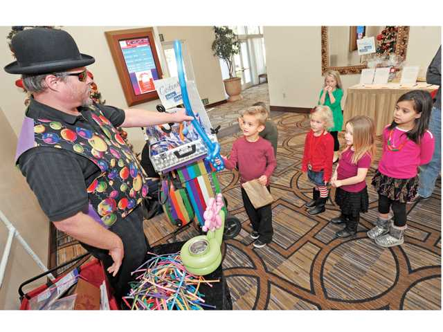 Cameron Pooley, 5, gets a balloon sword created by Dr. Popper Ph.D. (Keith Oberg), left, as he entertains at a Winter Festival event at the Hyatt Regency Valencia in December. Signal photo by Dan Watson.