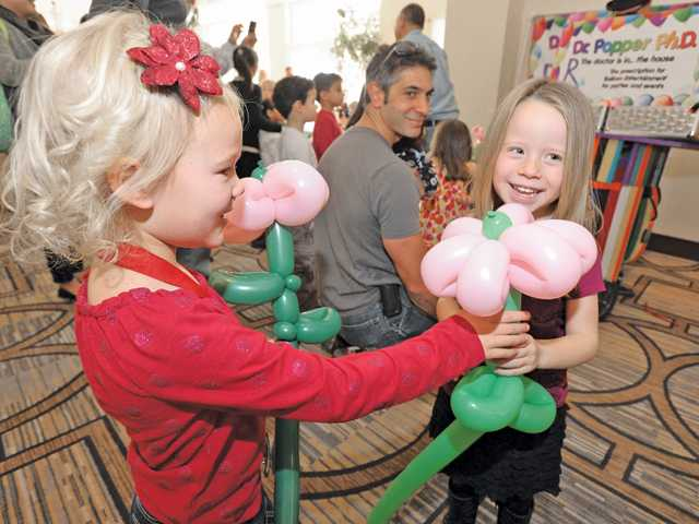 Charlotte Webster, 4, and Faith Webster, 4, compare balloon flowers created by Dr. Popper Ph.D. (Keith Oberg). Signal photo by Dan Watson.