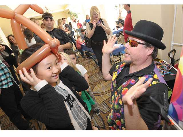 Jennifer Lee, 9, left, of Valencia reacts as she gets a set of balloon reindeer antlers created by Dr. Popper Ph.D., also known as Keith A. Oberg, right, as he entertains at a Winter Festival event held at the Hyatt Regency Valencia in December. Signal photo by Dan Watson.