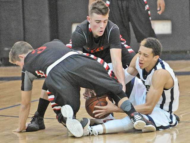 Hart players Chase White, left, and Andrew MacArthur, center, wrestle for a loose ball with Christian Ware-Berry, right, of West Ranch at West Ranch on Tuesday.