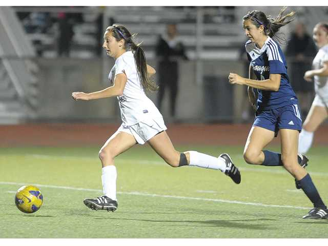 Valencia's Bailey Reid, left, outruns Saugus' Kaitlyn Benivedez to score the winning goal for Valencia in the final minutes of the game at Valencia on Tuesday.