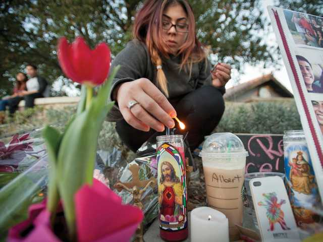 Leslie Montoya lights a candle at a memorial site for Albert Castro on the corner of Valencia Boulevard and The Old Road on Wednesday. Signal photo by Charlie Kaijo