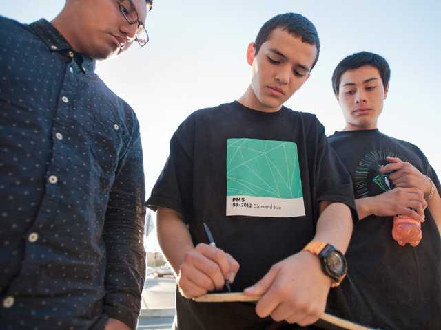 Joseph Aguilar signs a skateboard in dedication to Albert Castro with friends Jonathan Perez and Hanry Mejia during a memorial for Castro at Valencia Boulevard and The Old Road on Wednesday. Signal photo by Charlie Kaijo