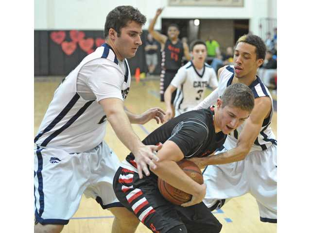 Hart's Chase White fights off a pair of West Ranch defenders on Tuesday night at West Ranch High.