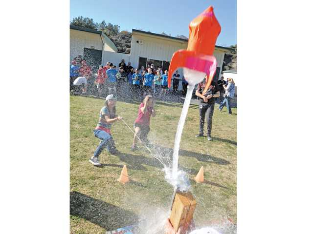 Sixth-graders Breeana San Lucas, left, and Isabella Chauncey launch their rocket named Solar Flair during the rocket-launch event held Friday at Santa Clarita Elementary School. Signal photo by Dan Watson