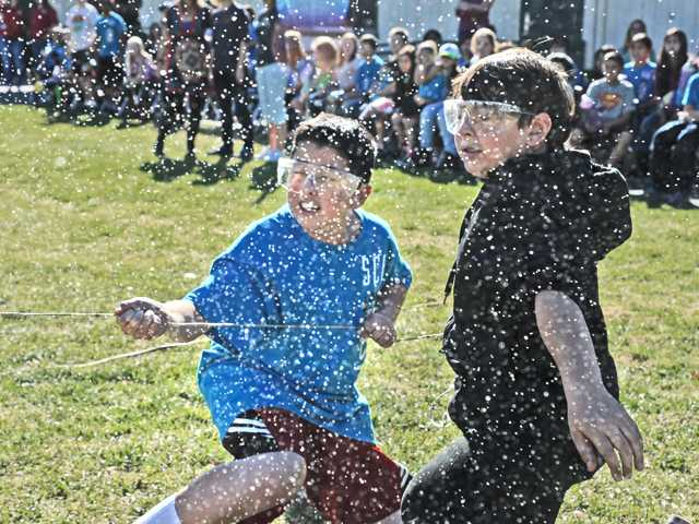 Rickie Hill, left, and Austin Hocutt are sprayed with water as they pull the release on their compressed air-powered plastic bottle rocket during the science event Friday afternoon at Santa Clarita Elementary School. Signal photo by Dan Watson