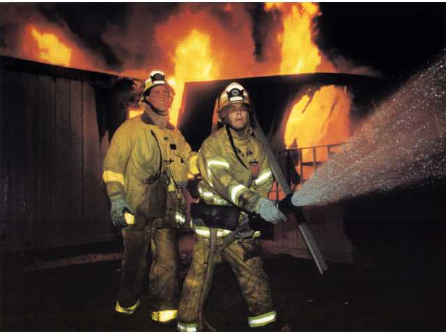 Firefighters Steve Toledo and Pat Perez battle a blaze at Greenbrier Mobile Home Park, where 14 homesburned to the ground when gas lines were severed by the earthquake.