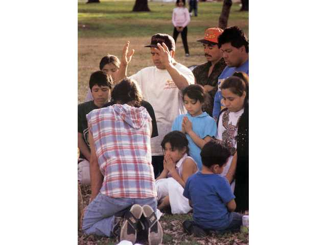 Florentino Avila of Newhall leads a group of campers in a prayer of thanks for their health. The group of residents camped at Newhall Park during the quake's aftermath.
