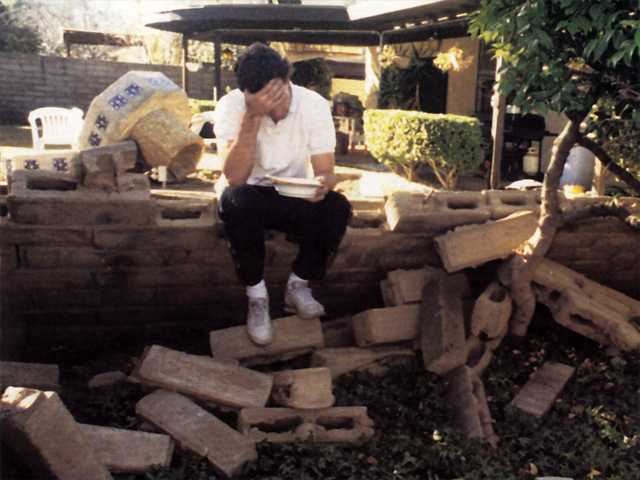 A resident sits in the rubble of what was a wall in front of his house after the quake hit the area in 1994.