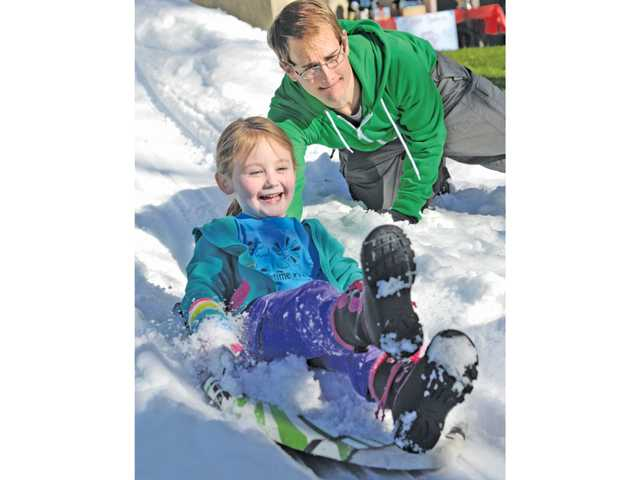 Elora Murdock, 5, of Valencia gets a push from her dad, Brad, as she rides a sled down a ramp of ramp at the YMCA open house event held at the YMCA in Valencia on Saturday. Dozens attended the open house and enjoyed a patch of snow, crafts and snow cones.
