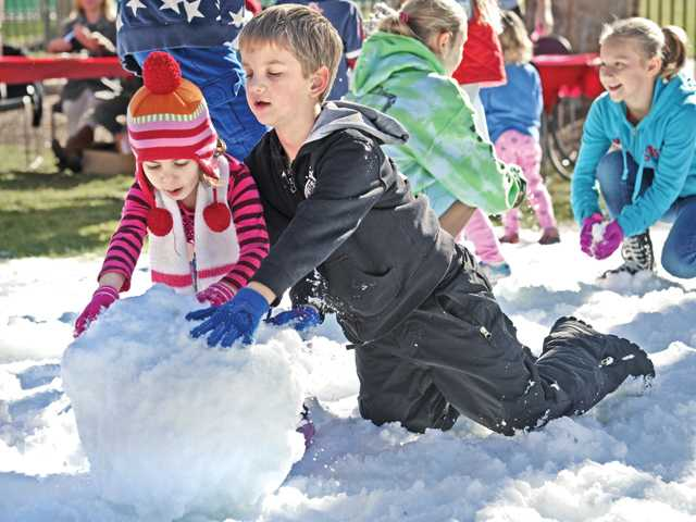 Natalie Ghadimian, 3, left, and Gavin Holmes, 7, of Valencia roll a snow ball at the YMCA open house event held at the YMCA in Valencia on Saturday. Dozens attended the open house and enjoyed a patch of snow, crafts and snow cones.