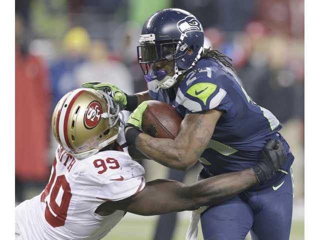 Seattle Seahawk Marshawn Lynch (right) stiff arms San Francisco's Aldon Smith on Sunday during the NFC championship game in Seattle.