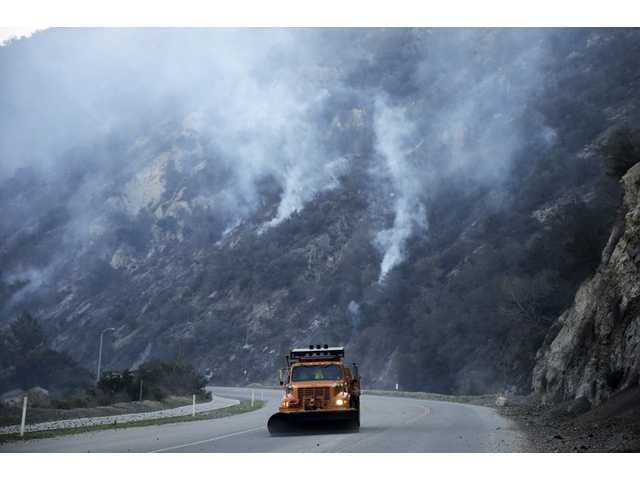 A truck clears away rocks along San Gabriel Canyon Road as firefighters continue to battle the Colby Fire on Friday near Azusa.